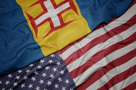 waving colorful flag of united states of america and national flag of madeira.