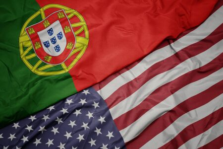 waving colorful flag of united states of america and national flag of portugal.