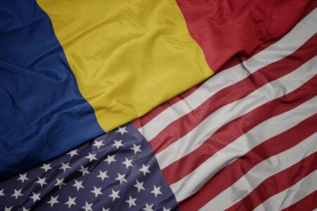 waving colorful flag of united states of america and national flag of romania.
