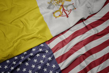 waving colorful flag of united states of america and national flag of vatican city.