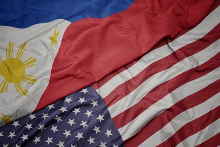 ondeando la colorida bandera de los estados unidos de américa y la bandera nacional de filipinas. macro Foto de archivo