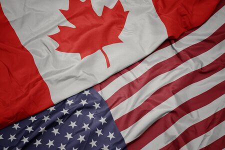 waving colorful flag of united states of america and national flag of canada. macro