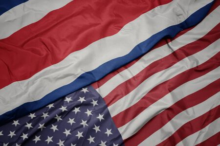 waving colorful flag of united states of america and national flag of costa rica. macro