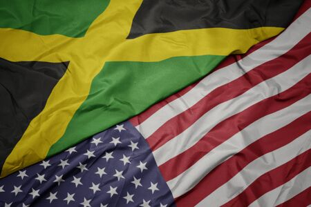 waving colorful flag of united states of america and national flag of jamaica. macro