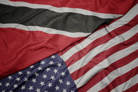 waving colorful flag of united states of america and national flag of trinidad and tobago. macro