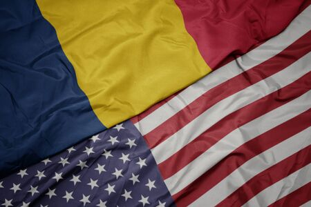 waving colorful flag of united states of america and national flag of chad. macro