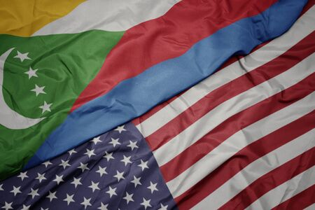 waving colorful flag of united states of america and national flag of comoros. macro