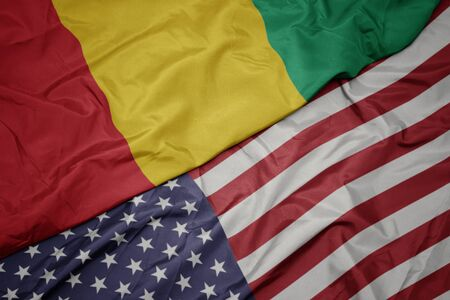 waving colorful flag of united states of america and national flag of guinea. macro