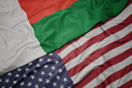 waving colorful flag of united states of america and national flag of madagascar. macro