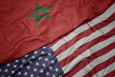 waving colorful flag of united states of america and national flag of morocco. macro
