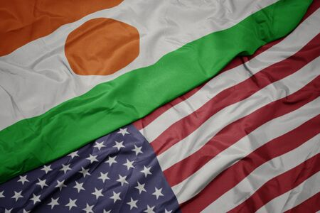 waving colorful flag of united states of america and national flag of niger. macro