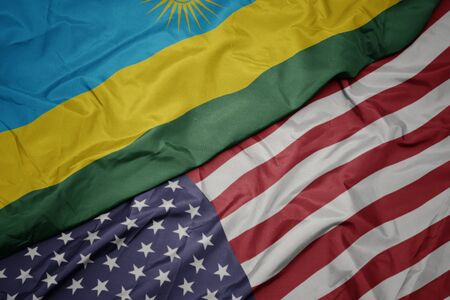 waving colorful flag of united states of america and national flag of rwanda. macro