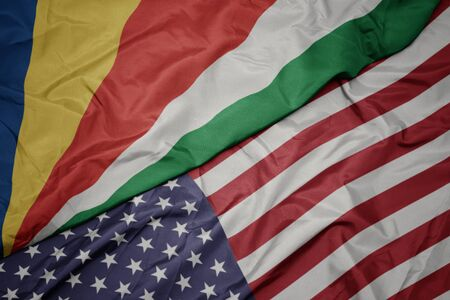 waving colorful flag of united states of america and national flag of seychelles. macro