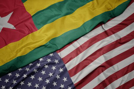 waving colorful flag of united states of america and national flag of togo. macro