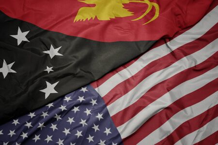 waving colorful flag of united states of america and national flag of Papua New Guinea. macro