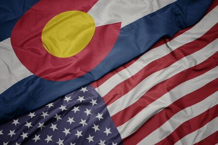 waving colorful flag of united states of america and flag of colorado state. macro