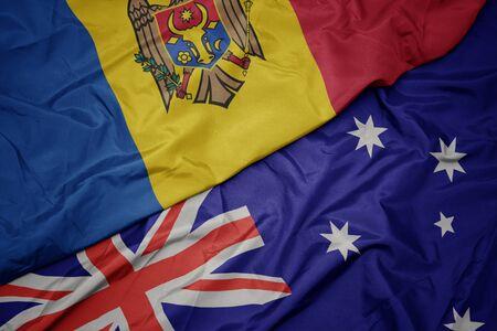 waving colorful flag of australia and national flag of moldova. macro