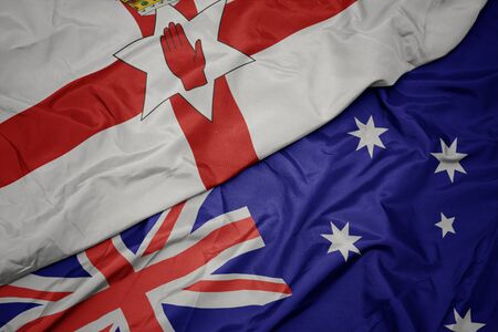 waving colorful flag of australia and national flag of northern ireland. macro