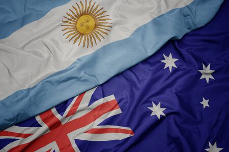 waving colorful flag of australia and national flag of argentina. macro