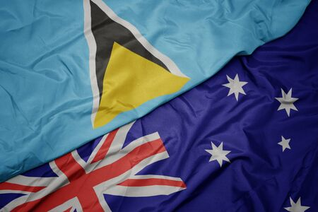 waving colorful flag of australia and national flag of saint lucia. macro