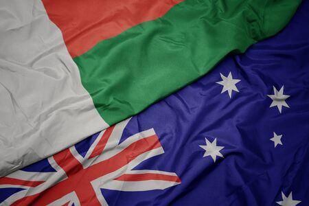 waving colorful flag of australia and national flag of madagascar. macro Фото со стока