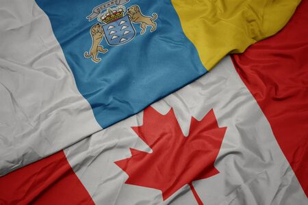 waving colorful flag of canada and national flag of canary islands. macro