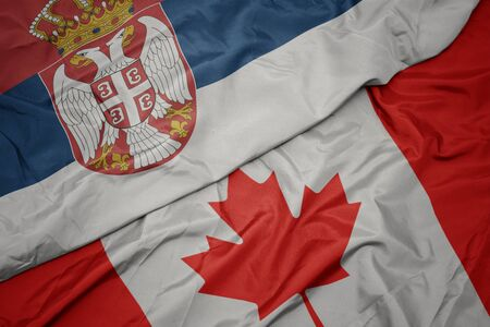 waving colorful flag of canada and national flag of serbia. macro