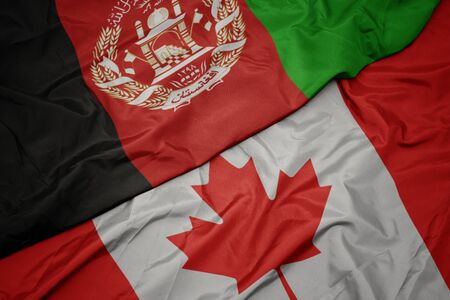 waving colorful flag of canada and national flag of afghanistan. macro