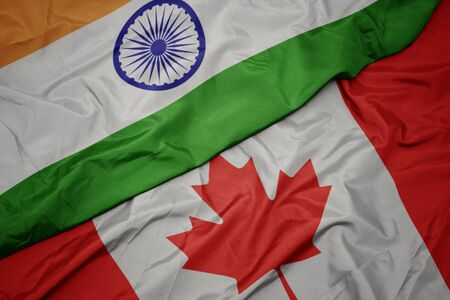 waving colorful flag of canada and national flag of india. macro Stock Photo