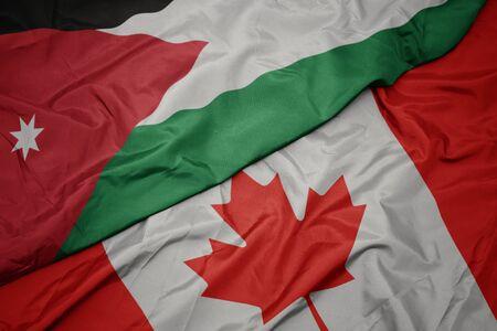 waving colorful flag of canada and national flag of jordan. macro Stock Photo