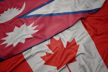 waving colorful flag of canada and national flag of nepal. macro Stock Photo