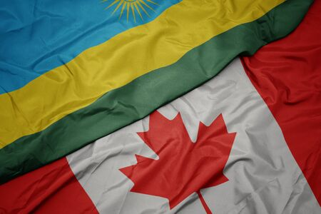 waving colorful flag of canada and national flag of rwanda. macro