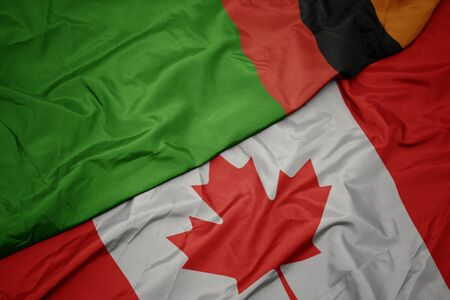 waving colorful flag of canada and national flag of zambia. macro Stock Photo