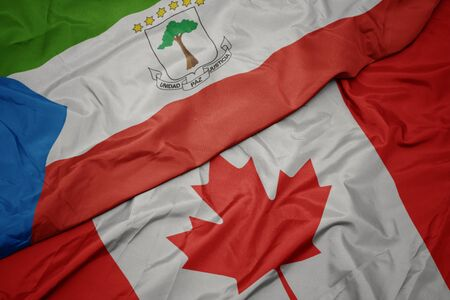 waving colorful flag of canada and national flag of equatorial guinea. macro
