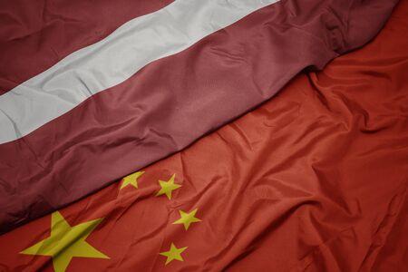 waving colorful flag of china and national flag of latvia. macro Banco de Imagens