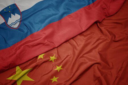 waving colorful flag of china and national flag of slovenia. macro
