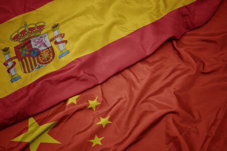 waving colorful flag of china and national flag of spain. macro Stock Photo