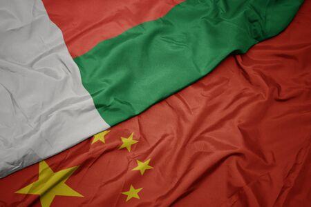 waving colorful flag of china and national flag of madagascar. macro Фото со стока