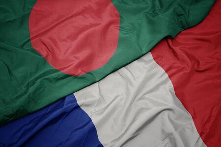 waving colorful flag of france and national flag of bangladesh. macro