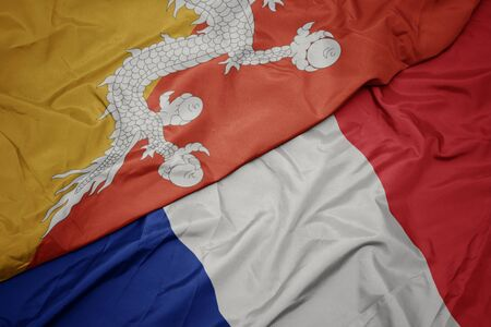 waving colorful flag of france and national flag of bhutan. macro