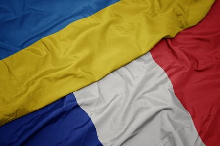 waving colorful flag of france and national flag of ukraine. macro