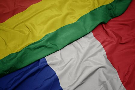 waving colorful flag of france and national flag of bolivia. macro