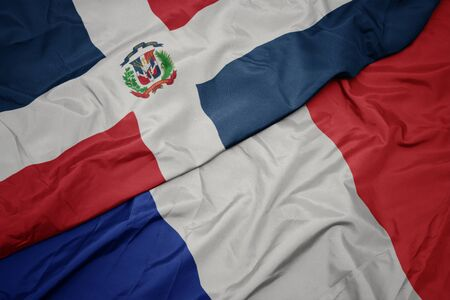 waving colorful flag of france and national flag of dominican republic. macro