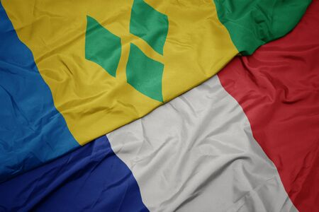 waving colorful flag of france and national flag of saint vincent and the grenadines. macro