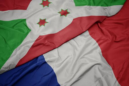 waving colorful flag of france and national flag of burundi. macro Stockfoto