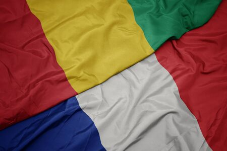 waving colorful flag of france and national flag of guinea. macro Stockfoto