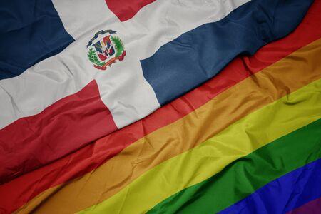 waving colorful gay rainbow flag and national flag of dominican republic. macro Фото со стока