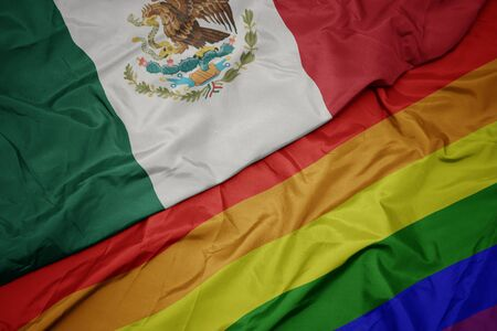 waving colorful gay rainbow flag and national flag of mexico. macro
