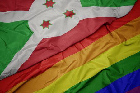 waving colorful rainbow flag and national flag of burundi . macro Stock Photo