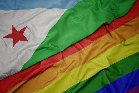 waving colorful gay rainbow flag and national flag of djibouti. macro Stock Photo